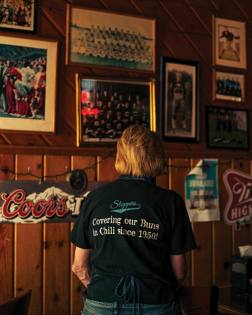 "Back of a woman with a shirt that says ""covering our buns in chili since 1950."""