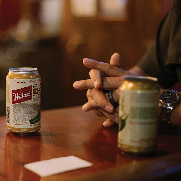 Close up of beer cans with folded hands