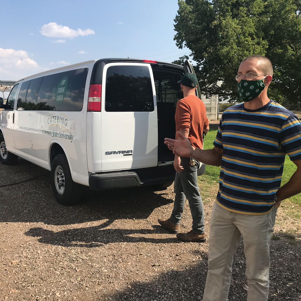 Man in a mask stands behind a white van.