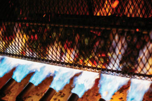 Chiles in a metal cage being hit with jets of blue flame.