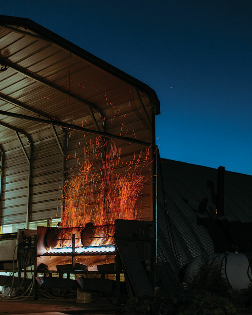 Sparks come off a roaster into the night sky