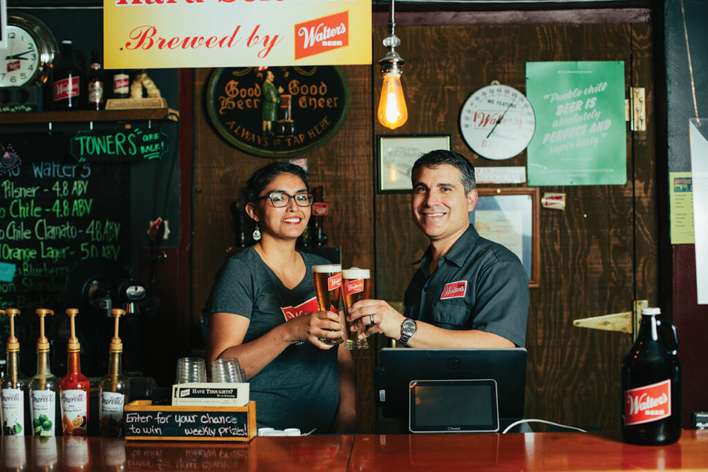 Man and woman clink glasses behind a bar.