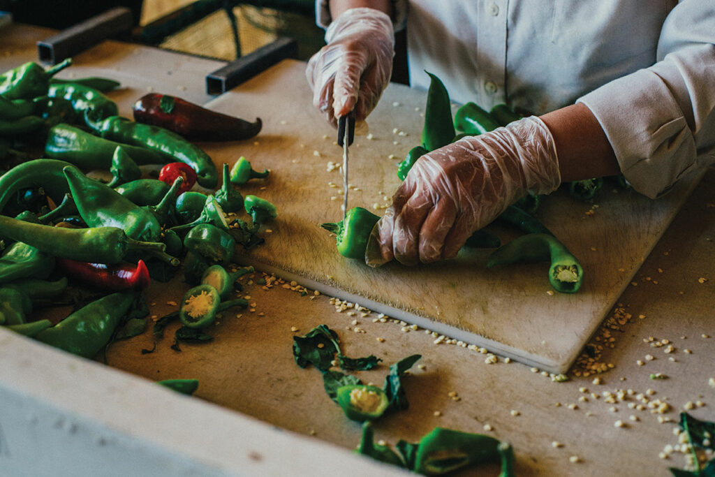 Close up of hands slicing chiles