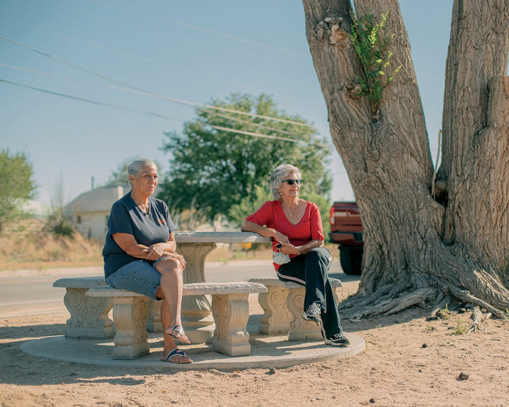 Two people sit at a stone table and chairs