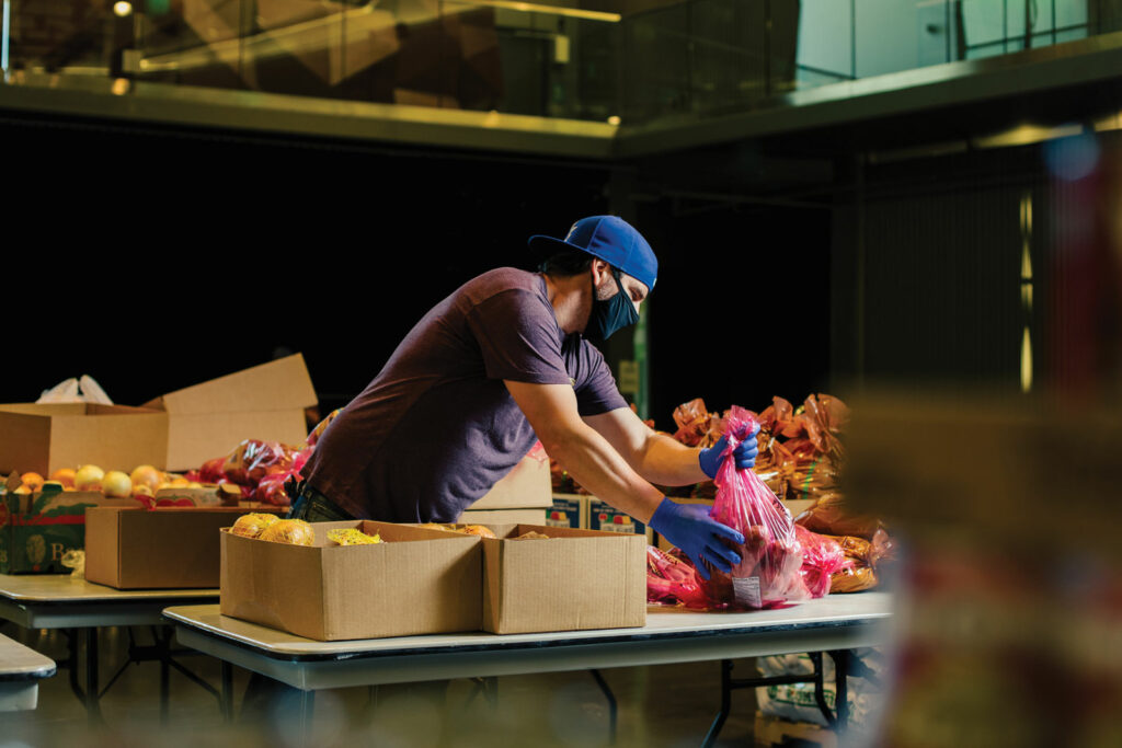 Man in a mask packs boxes of food.