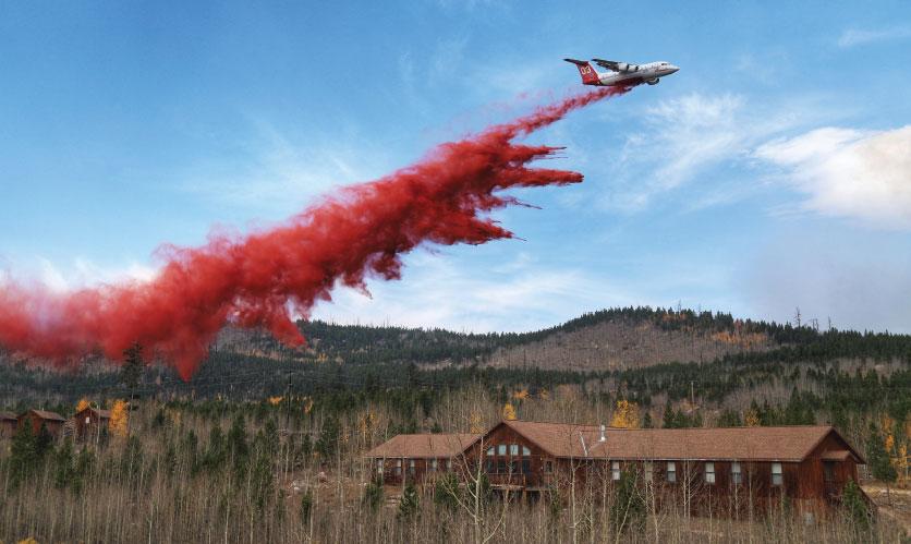 Airplane drops bright red retardant