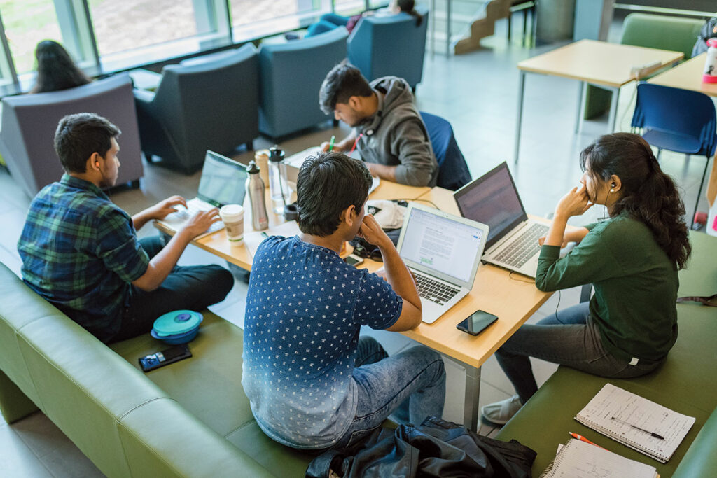 Overhead shot of students working on laptops at a communal table.